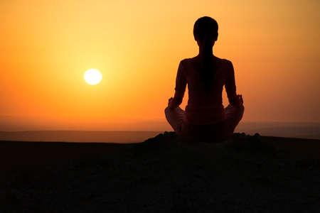 Girl practicing yoga at sunrise, outdoor sun Stock Photo
