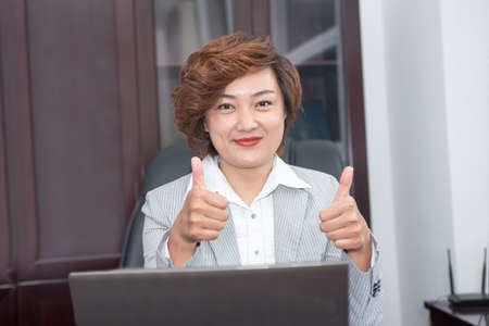 praised: Business woman thumbs up with both hands, praised the success
