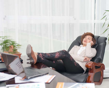 Female business people lying on the chair to call  photo
