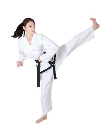 arts: Woman practicing taekwondo isolated on white