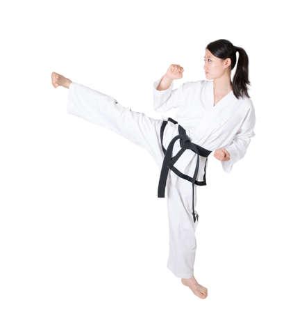 Woman practicing taekwondo isolated on white