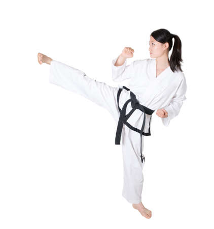 Woman practicing taekwondo isolated on white  photo