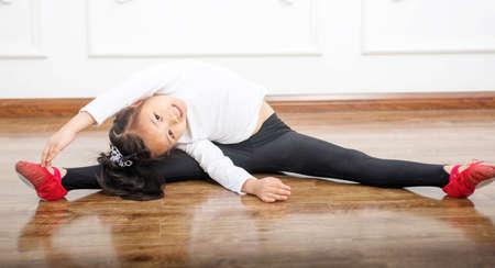 little girl doing sports exercises on the mat