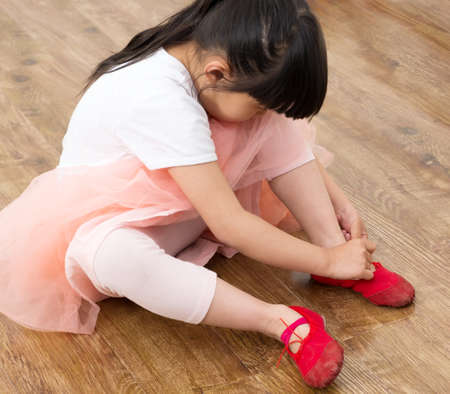 Little brunette girl trying on ballet shoes