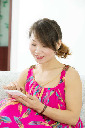 Smiling woman with smartphone at home. Asian Girl photo