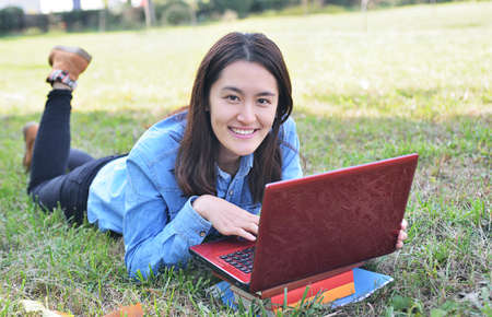 College student using laptop on campus lawn photo