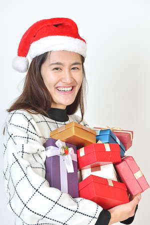 armful: Asian woman with an armful of presents after going Christmas shopping. isolated on a white background Stock Photo