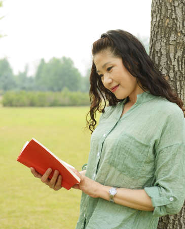 rely: Beautiful old woman reading a book. Rely on Park trees Stock Photo