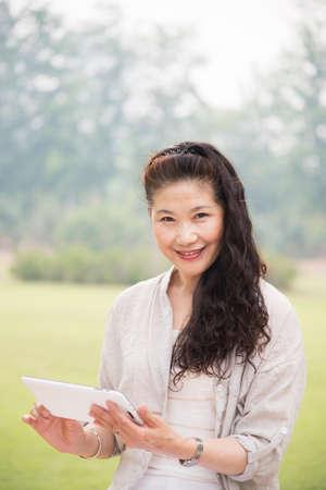 pcs: Happy elderly woman using Tablet PCs in the Park