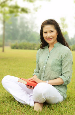 Beautiful woman holding a book sitting on the grass in the Park 免版税图像