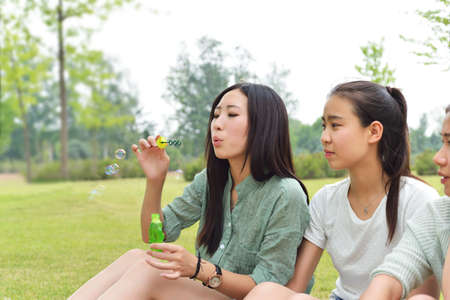 adult toys: Two ladies sitting on the lawn playing with bubbles Stock Photo