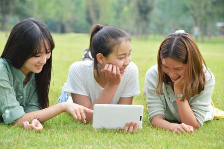 prone: Three lovely girls lie prone on the grass.Use the tablet