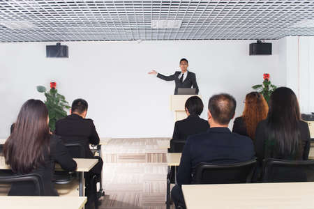confer: business man giving a conference in a room