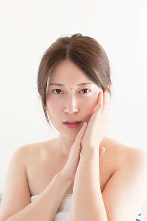 woman posing with her hands to her cheeks and bare shoulders looking directly at the camera