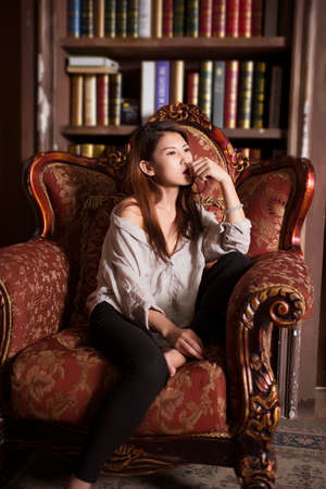 Sexy Asian woman sat in an armchair.