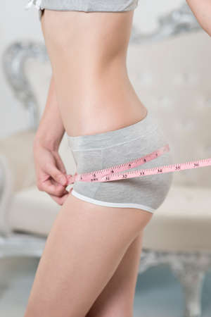 Woman measuring her waist with a  measuring tape Stock Photo