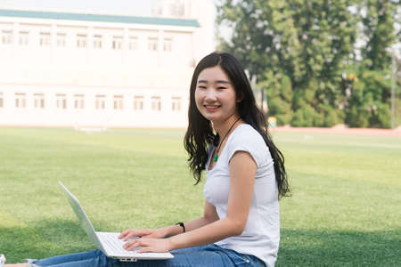 Beautiful Asian college student with laptop ,Sat on the playground. Stock Photo