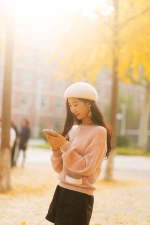 Portrait of a smiling pretty woman texting on an autumn day Banco de Imagens