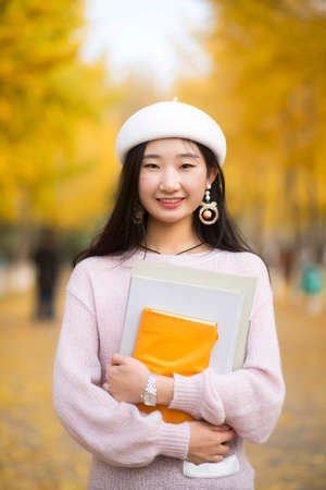 Portrait of a smiling pretty woman holding books in hand