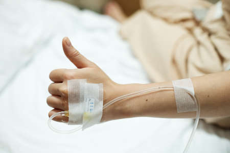 病院のベッドで生理食塩水の点滴点滴しながら与えられた患者の手の親指