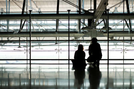 Silhouette of man and woman travelers waiting for plane at airports hallway
