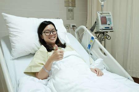 Asiatiques pouces patients fille vers le haut et le sourire en position couchée sur le lit d'hôpital Banque d'images - 50202332
