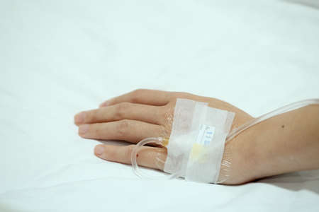 injected: Patient hand injected with saline IV drip on hospital bed