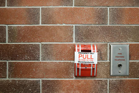 fire brick: Emergency fire alarm switch on red brick wall background