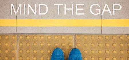 駅のプラットフォームの端に描かれた「段差に注意」看板 写真素材