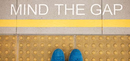 The sign  Mind the gap  painted on train stations platform edge