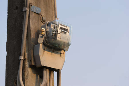 Electric meter on electrical pole, sunset sky background with copy space