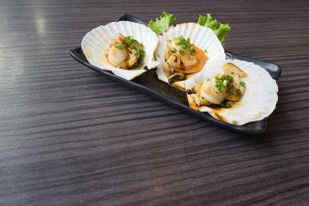 hotate: Three raw scallops on teriyaki sauce, copy space on the table