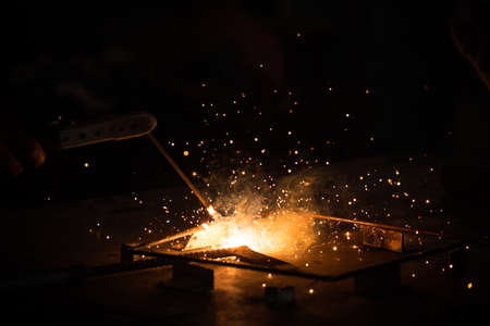 metal working: Welding, metal working on dark background, with golden flare and bokeh of sparks