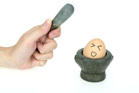 crush on: Egg on mini kitchen mortar, afraid of getting crush, isolated on white background Stock Photo