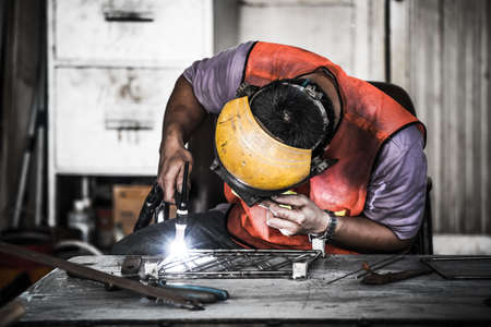 Industrial workers: HDR image of a technician using tig welder in factorys workshop