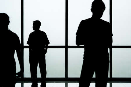 people shadow: Silhouette of people in front of glass wall background, abstract image