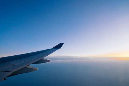 夜明けの空の背景に飛行機の翼
