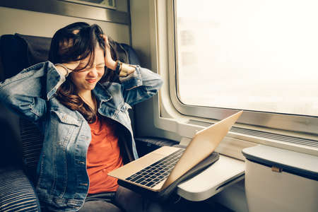 Asian college girl frustrated with laptop on the train, warm light tone, with copy space