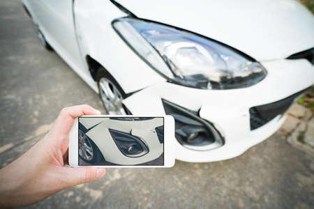 スマート フォンで破損した白い車の男撮影 写真素材