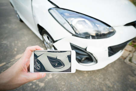 Man taking photo of damaged white car with smartphone Foto de archivo