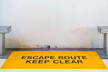 clear path: Escape route, keep clear sign blocked by concrete wall with copy space, clipping path for travel image adaptation