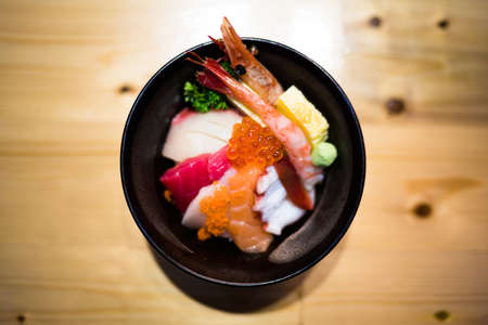 hotate: Chirashi sushi, Japanese food rice bowl with raw salmon sashimi, mixed seafood, top view, darken edge, center aligned with copy space on wooden table, focus on salmon eggs with depth of field effect