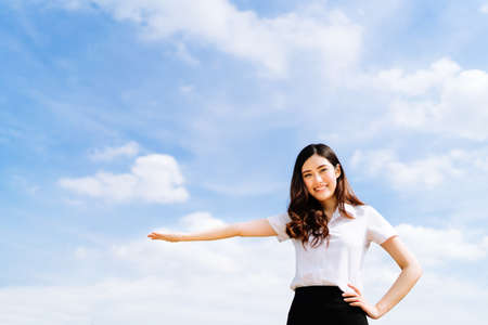 Beautiful young asian university or college student woman doing advertising or product presenting pose, copy space on blue sky background, education or job or advertisement concept