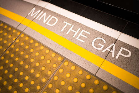 Mind the gap sign painted on train stations platform edge, conceptual, vignette darken edge, depth of field blur on far end Stock Photo