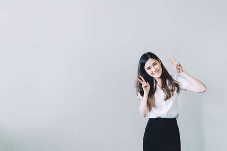 asian bunny: Cute asian university girl doing funny rabbit pose, copy space on gray wall background