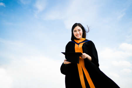 Beautiful asian university or college graduate student woman smiling in graduation academic dress on gown, education or success concept, copy space on blue sky background
