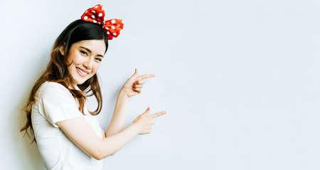 아름 다운 아시아 대학이나 대학 학생 여자 화이트 보드 배경 복사 공간을 가르키는 재미 있은 활 머리 띠를 입고