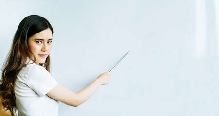 Beautiful asian woman using pointer on shiny whiteboard, serious or angry face, with copy space, focus on the eye, concept of teacher, tutor, student, or businesswoman