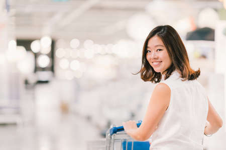 Beautiful young Asian woman smiling, with shopping cart, shopping center or department store scene, blur bokeh background with copy space, shopping or shopaholic concept