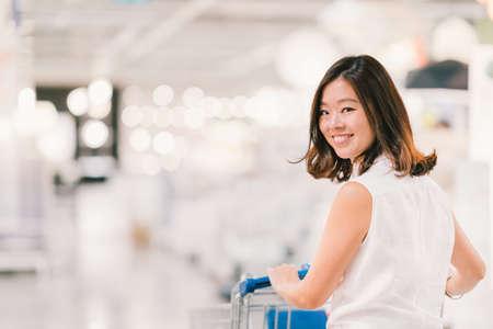 Mooie jonge Aziatische vrouw lachend, met het winkelwagentje, winkelcentrum of warenhuis scene, blur achtergrond met kopie ruimte, winkelen of shopaholic begrip